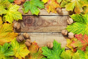 Autumn leaves nuts over old wooden background