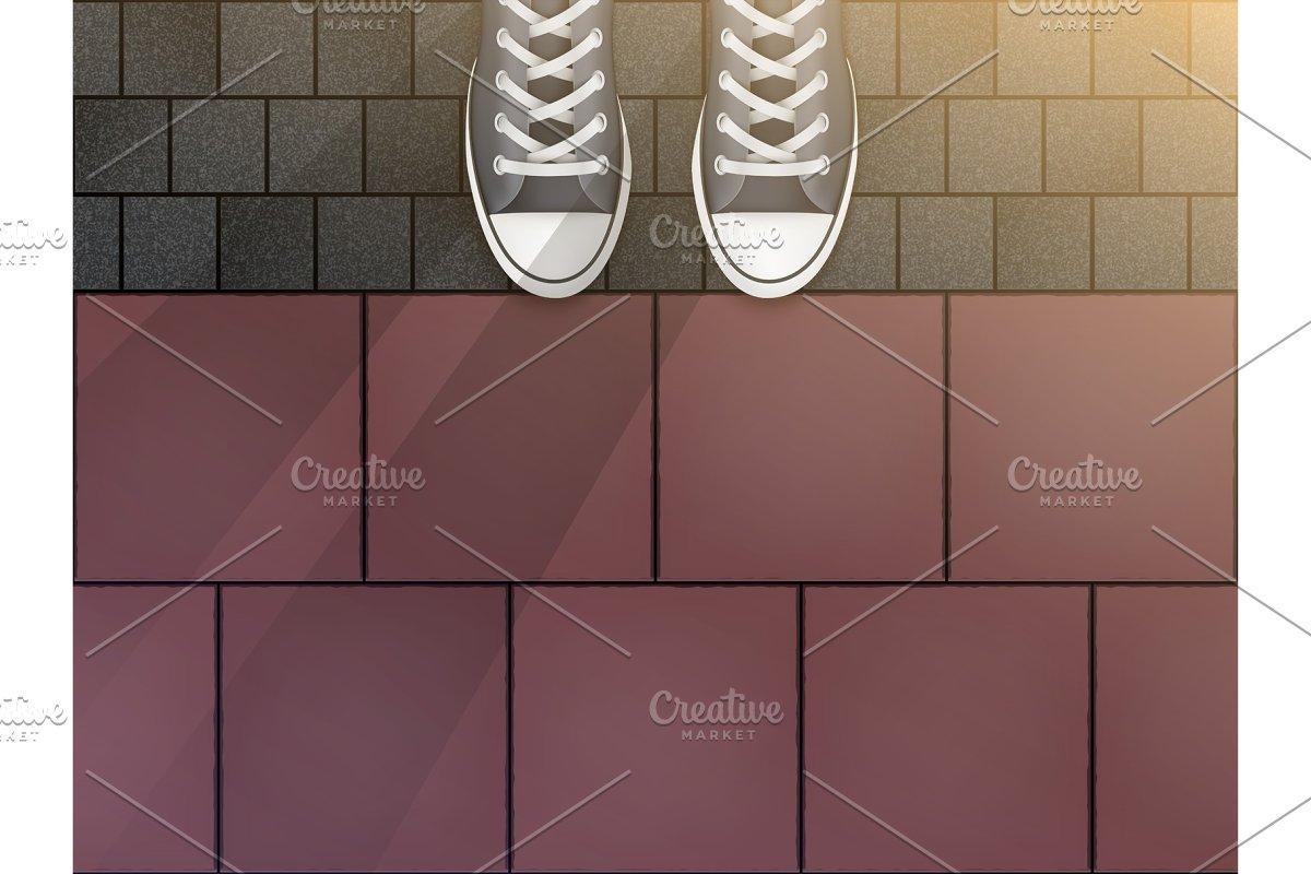 Feet in sneakers on cobblestone
