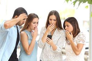 Four worried friends watching smart phone.jpg