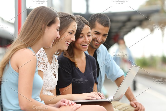 Four friends using a laptop in a train station.jpg - Technology