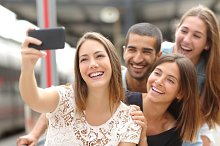 Group of four friends taking selfie with a smart phone.jpg