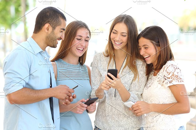 Four friends watching social media in a smart phone.jpg - Technology