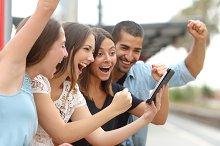 Four euphoric friends watching a tablet.jpg