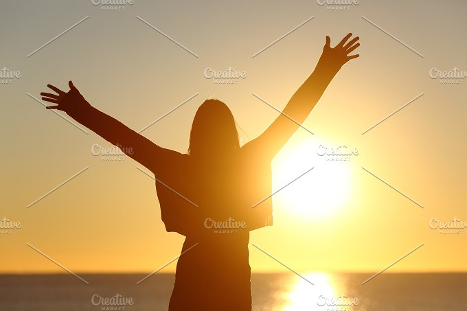 Free woman raising arms watching sun at sunrise.jpg - Health