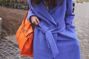 Woman in blue coat with bag