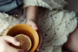 Yellow Cup of tea in hand of girl
