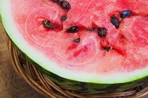 Cut in half watermelon on old wooden table. Red ripe fruit wood background  top view image
