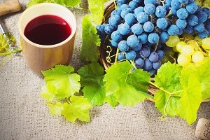 red wine and grapes in vintage setting with corks on wooden table