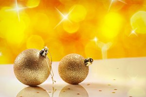 Two golden balls and yellow bokeh