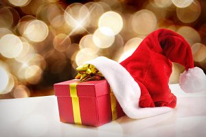 Santa Claus hat with gift golden background and diagonal view.jpg