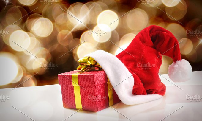 Santa Claus hat with gift golden background and diagonal view.jpg - Holidays