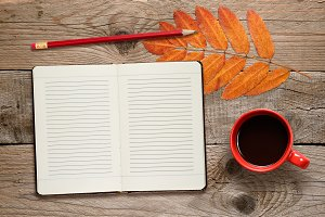 Coffee cup, open diary and pencil