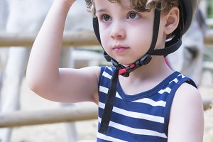 boy rider adjusts his helmet