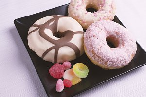 Donuts and candy on a black plate
