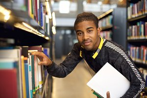 Young man getting books from library