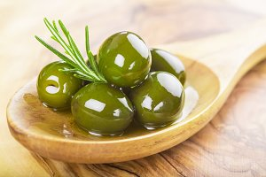 Green olives in a wooden spoon