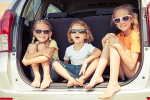 happy children sitting in car