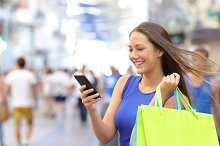 Shopper shopping with smartphone in the street.jpg