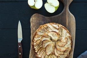 Apple pie on dark chopping board