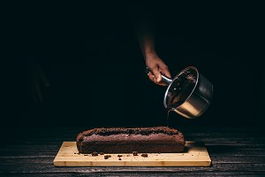 Pouring chocolate on a cake