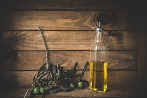 Olive oil with olives on wooden boar