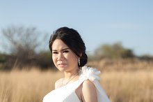 Bride standing in a meadow.