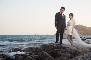 Bride and groom standing on rocks.