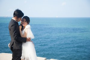 bride and groom standing by the sea.