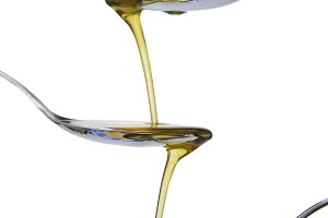Olive oil falling between the spoons