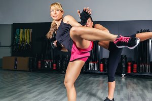 Women training kick boxing in gym