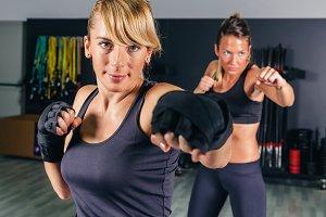 Women training hard boxing in gym
