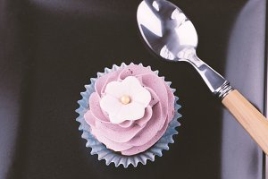 Cupcake and spoon on black dish