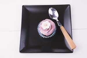 Cupcake and a spoon on a black plate