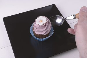 Hand with spoon on a cupcake