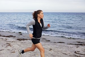 Female runner running on seashore