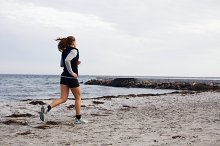 Fit young woman jogging along shore