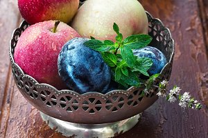 apples and plums in iron vase