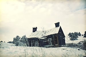 abandoned wooden house in snow