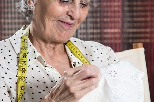 happy senior woman sewing
