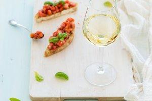 Glass of white wine and bruschettas