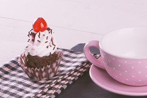 Cupcake over napkin point to a cup