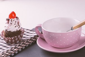 Cupcake with cup, plate and spoon