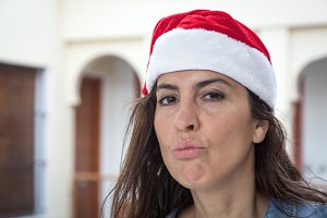 Brunette woman with red Christmas ha
