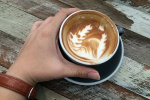 hand holding cup of latte coffee