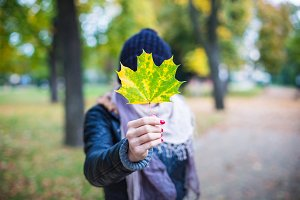 Young Girl Holding Autumn Fall Leaf