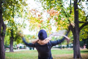 Girl Throwing Fall Leaves in The Air