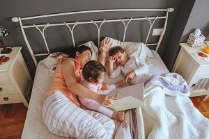Mother reading book to sons in a bed