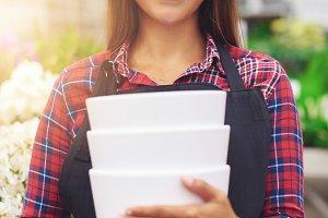Woman holding flowerpots