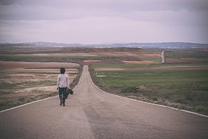 Woman walking alone in a road