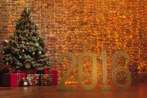 Letters '2016' and decorated Christmas tree on brick wall background